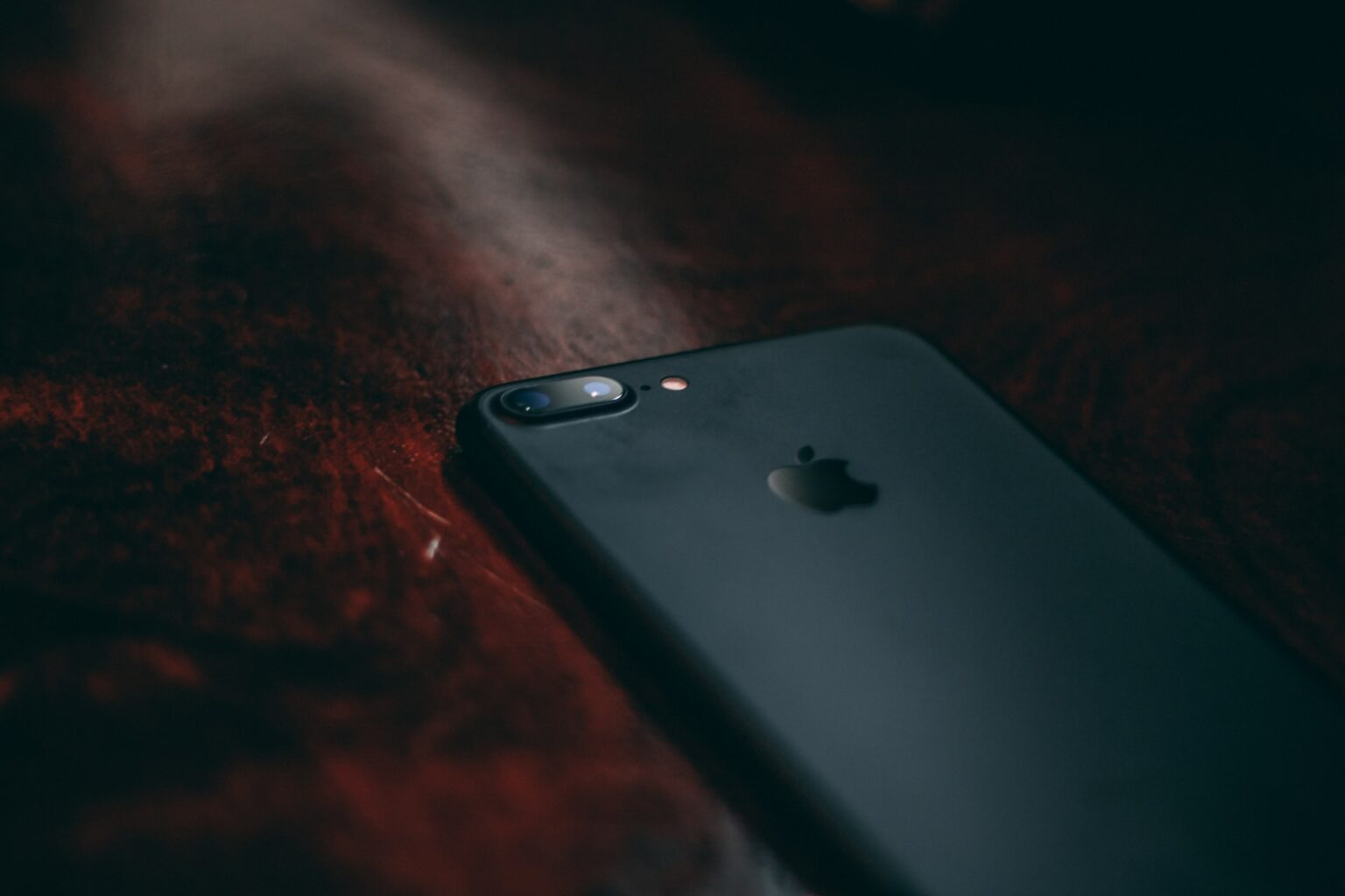 iphone on a dark wood background, illustrating the article is smartphone use killing their sperm