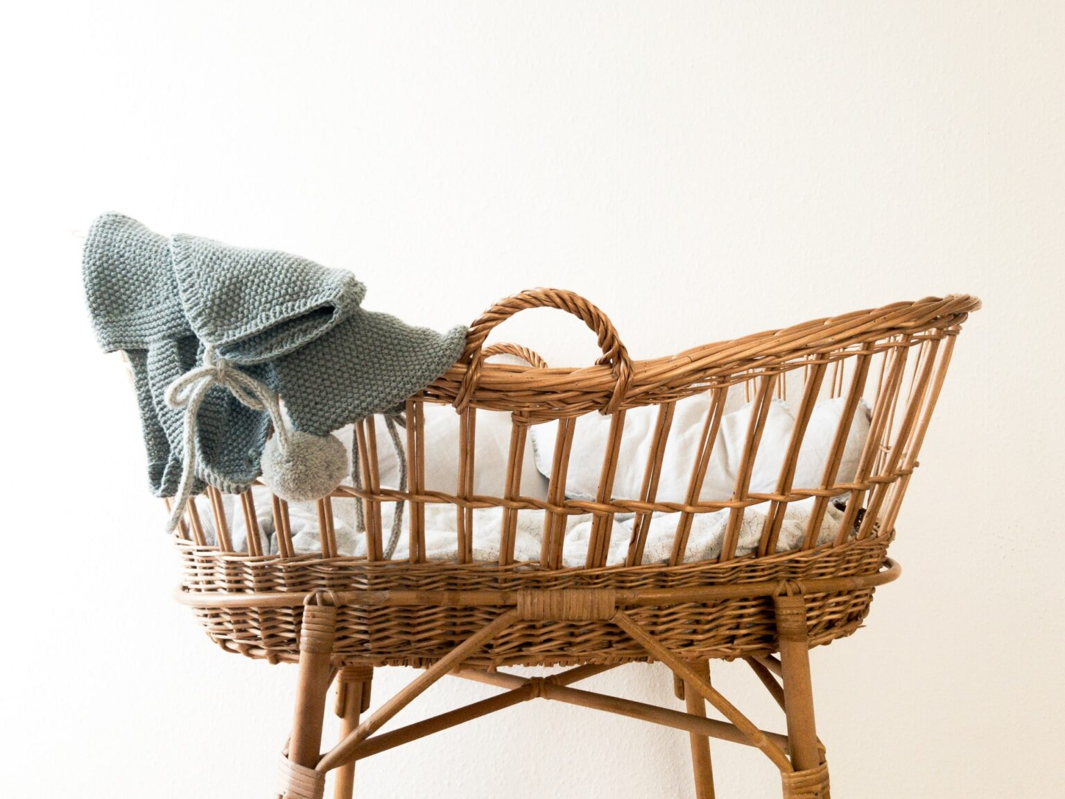 wooden baby crib with a grey blanket illustrating surrogacy article best fertility now