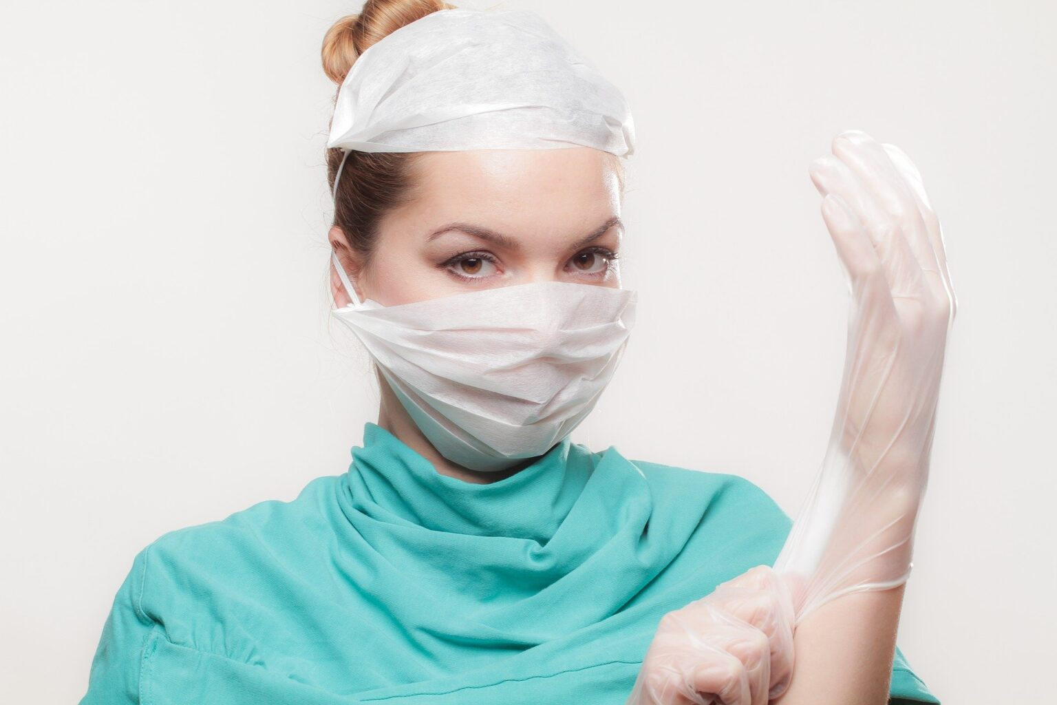 female doctor in green scrubs and a face mask, putting on white gloves illustrating best fertility now smear test article