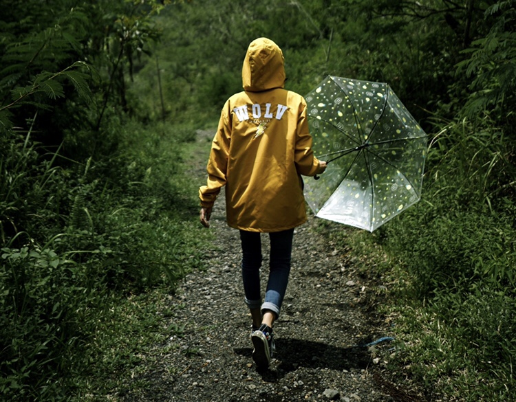 woman in yellow rain jacket, holding a clear umbrella illustrating life with endometriosis best fertility now