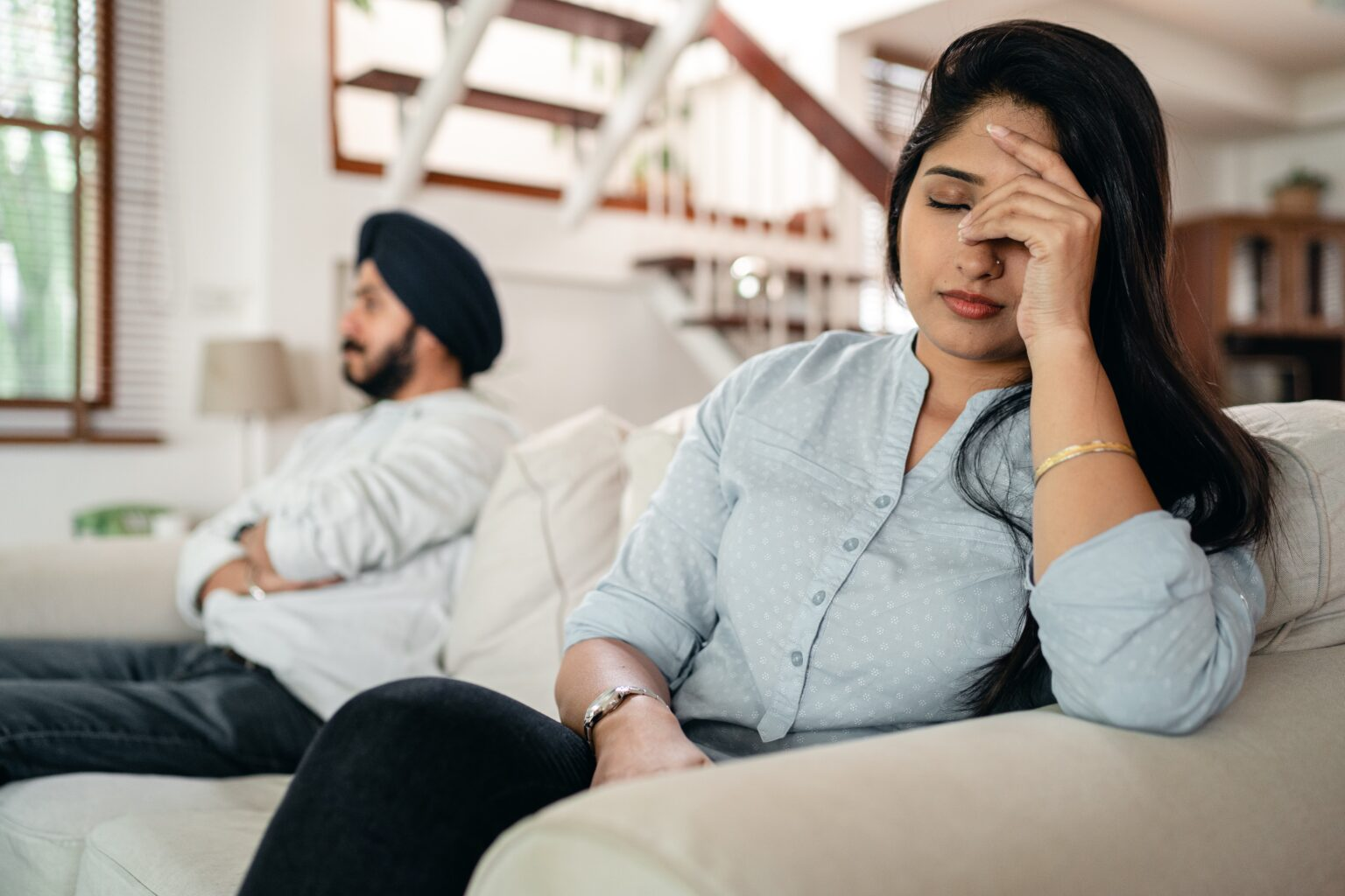 sikh man in a black turban sat on a sofa with a woman who is holding her head in her hands, illustrating the atrcilve can stress cause infertlity