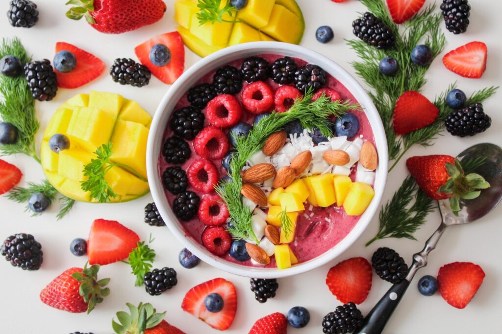 central white bowl with a red smoothie and vibrant tropic fruit and berries arranged atrtically in a curve illustrating Best Fertility Now Raw Vegan food article