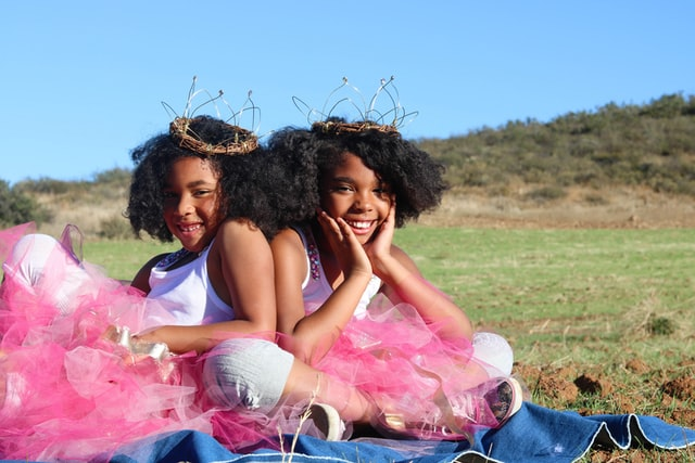 twin black girls, smileing in pink tutu's, on a green hillside, the twins are wearing brown twisted twig crowns, illustration best fertility now ivf twins article