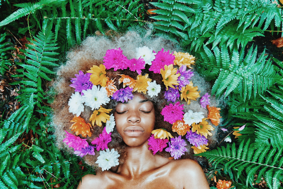 black woman laying on a bed of large geen leaves witl pink white and orange flowers in her natural hair illustrating avoiding BPA for fertility