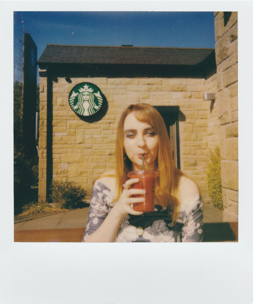 woman holding an iced coffee infront of a starbucks shop illustrating caffeine causing miscarriages