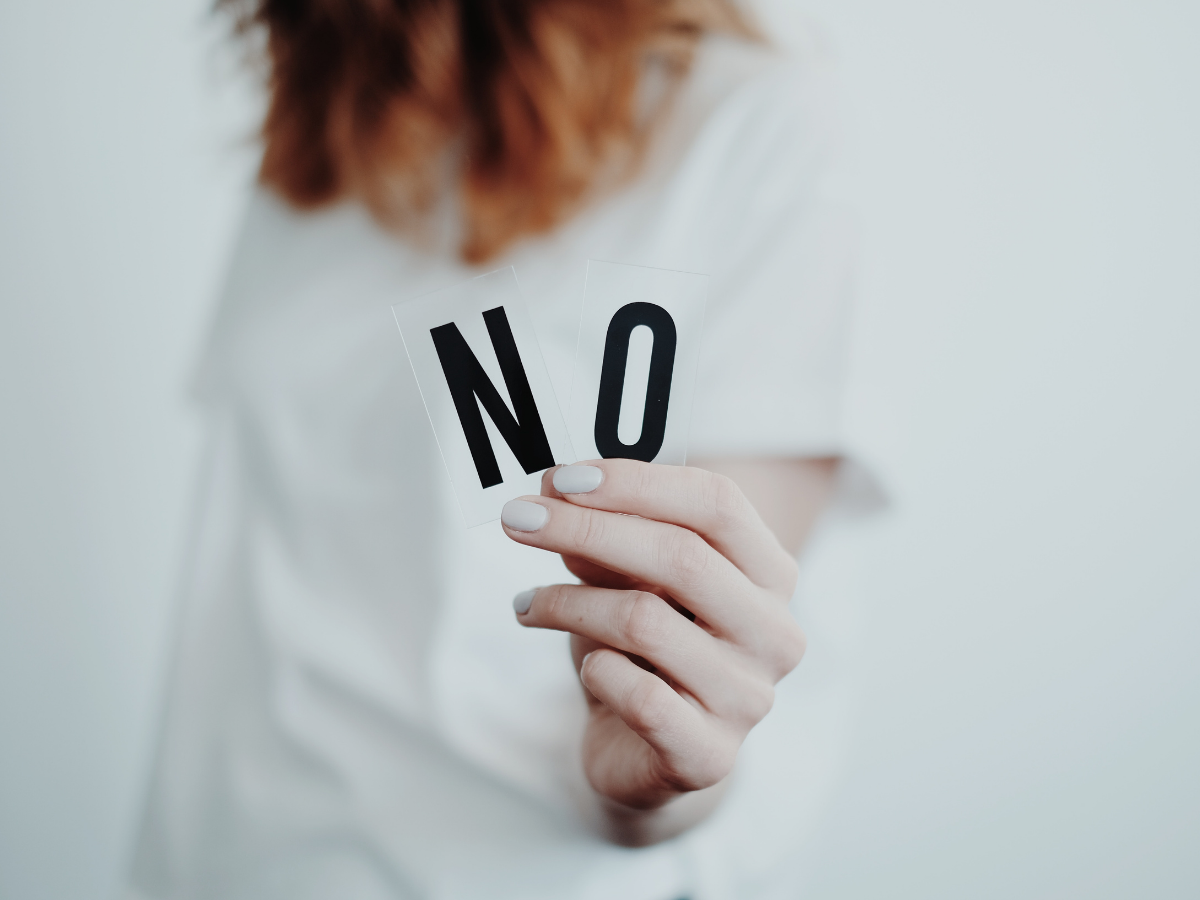 woman with red hair in a white jumper out of focus holing a black NO up to the front of the image that is in focus illustrating Endometriosis cures that dont work on best fertility now