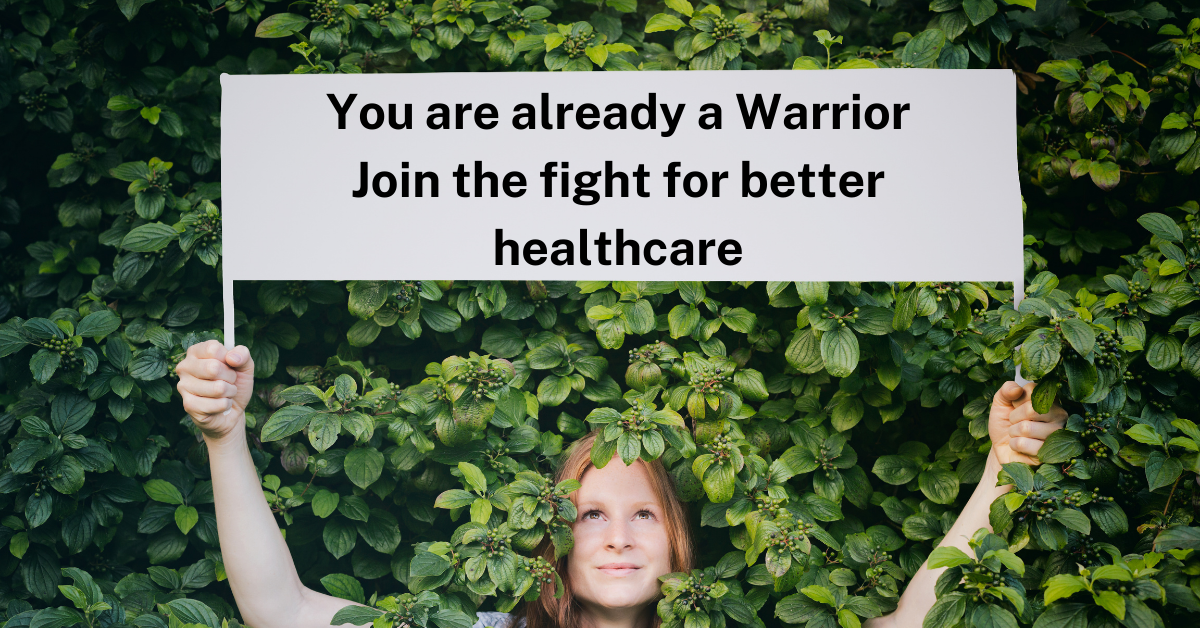 red haired woman deep in green leaves, holding a sign that says you are already a warrior join the fight for better healthcare illustrating the fertility activism article on best fertility now