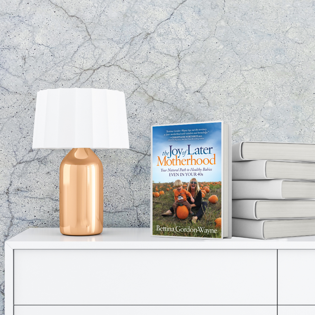The Joy of Later Motherhood: Your Natural Path to Healthy Babies Even in Your 40's book on a white chest of draws and a gold lamp to the left with a white lampshade