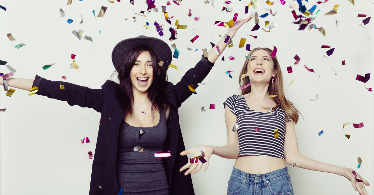two women celebratying with glitter strands falling from the sky would you do surrogacy for your best friend
