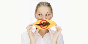 white woman on a plain background holing a papaya infront of her mouth, there is a red do not eat circle over the papaya illustrating the do not eat papaya for fertility reasons
