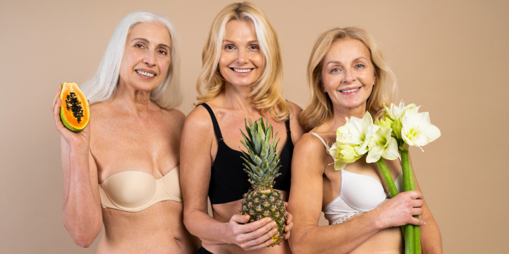 Geriatric and pregnancy three older women holding fertility symbols, a ppaya, a pineapple and a calli lilly