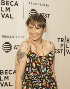Lena Dunham in a black and multicolour leaves dress, illustrating Celebrities with endometriosis